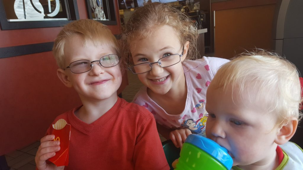 blond preschool boy in glasses curly hair pre-school girl in glasses toddler boy drinking from cup smiling Homeschool Pre-K