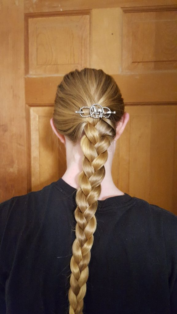 Lilla Rose Hair Accessories review back of woman's head with long blonde hair braided and a Lilla Rose horse flexi clip figure 8 hair clip above braid