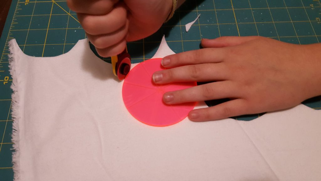Cotton rounds tutorial image hands using a circle ruler stencil and rotary cutting tool to cut fabric on a cutting mat