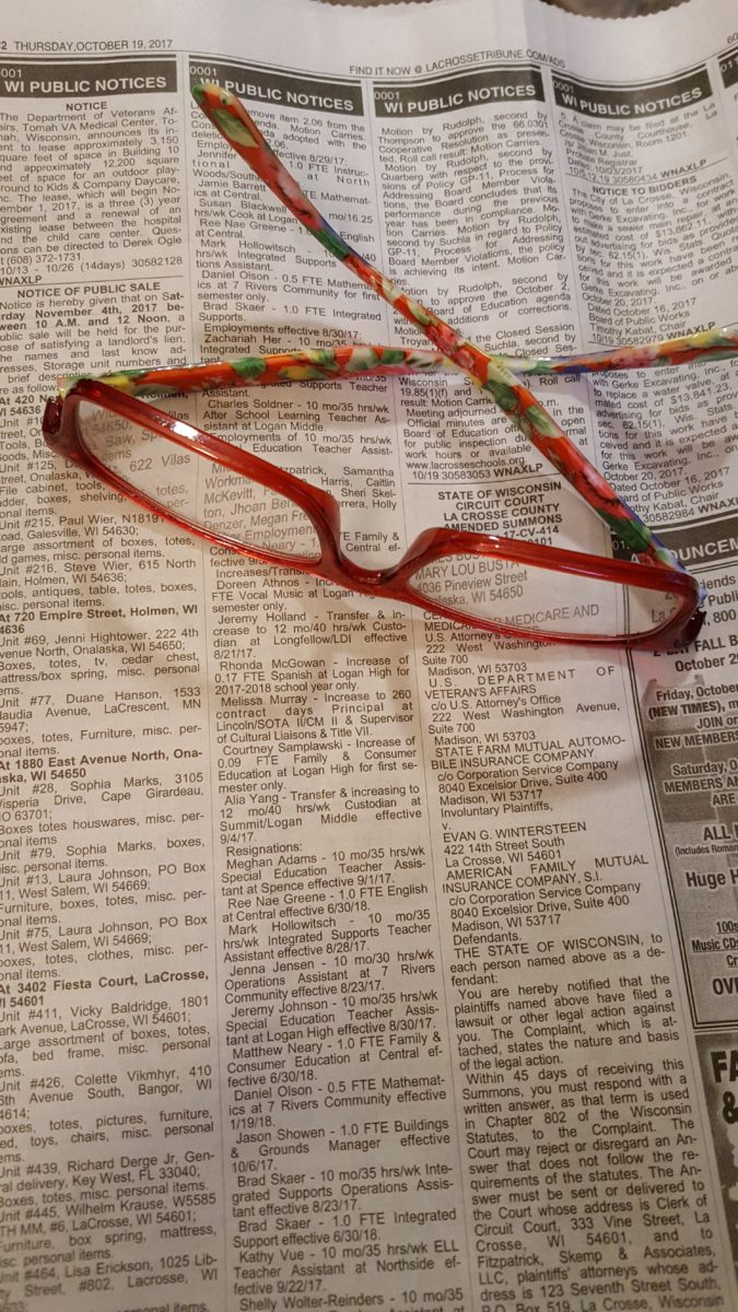 Two auctions at the same time glasses resting on a newspaper with listings of defaulted storage unit auctions