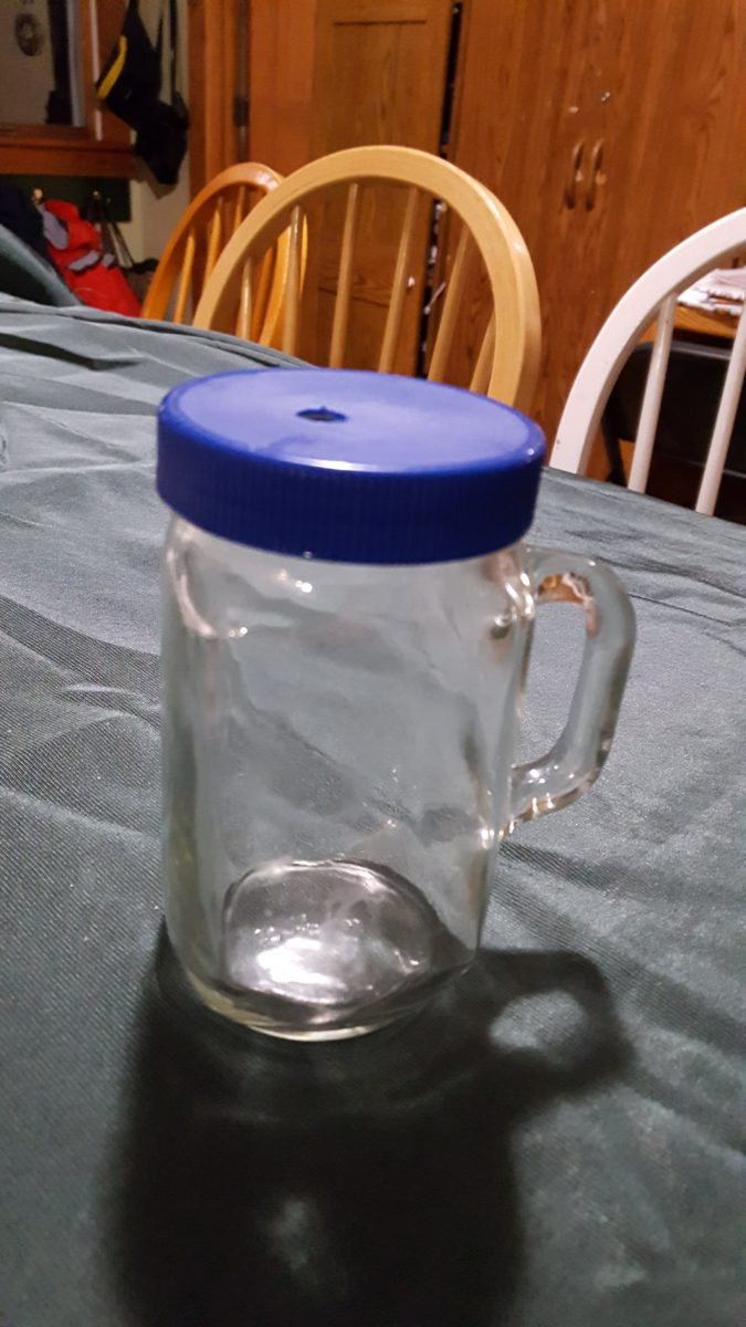 DIY White Elephant gifts - glass jar with handle and plastic lid with straw hole on a table