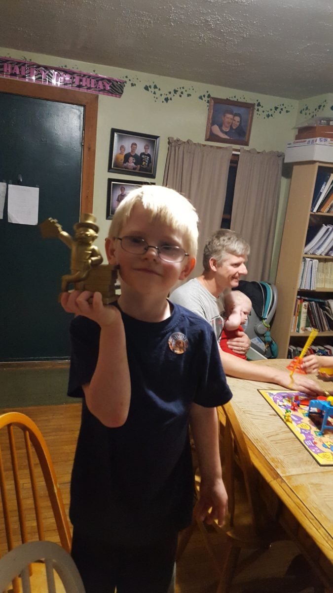 Family Game Night Large Family Style family game night winner boy holds plastic Mr. Moneybags trophy after Mousetrap