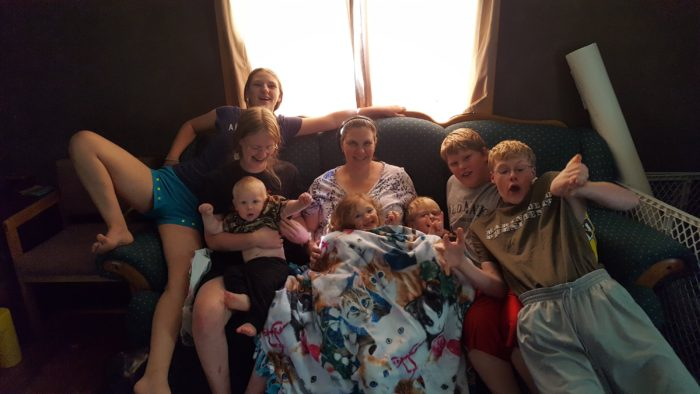 A typical day for a homeschooling large family mom of seven kids a mom with seven children sitting on a couch large family style