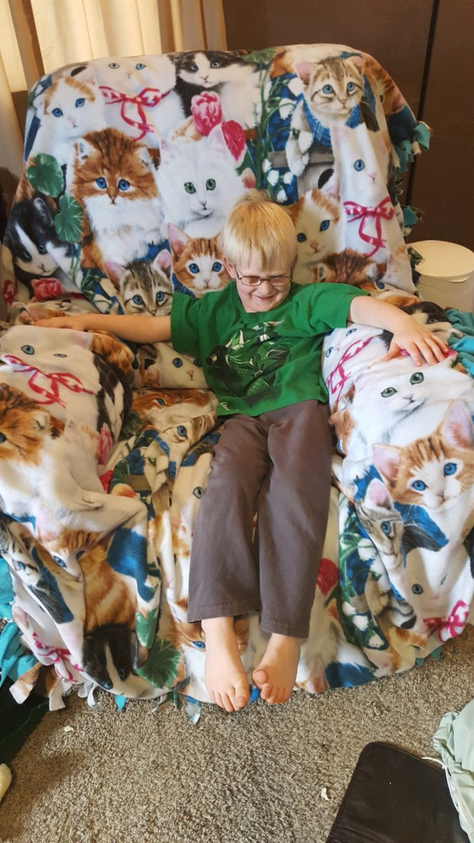A Day in the life of a mom of seven 5 year old boy wearing glasses sitting in a rocking chair on a cat blanket