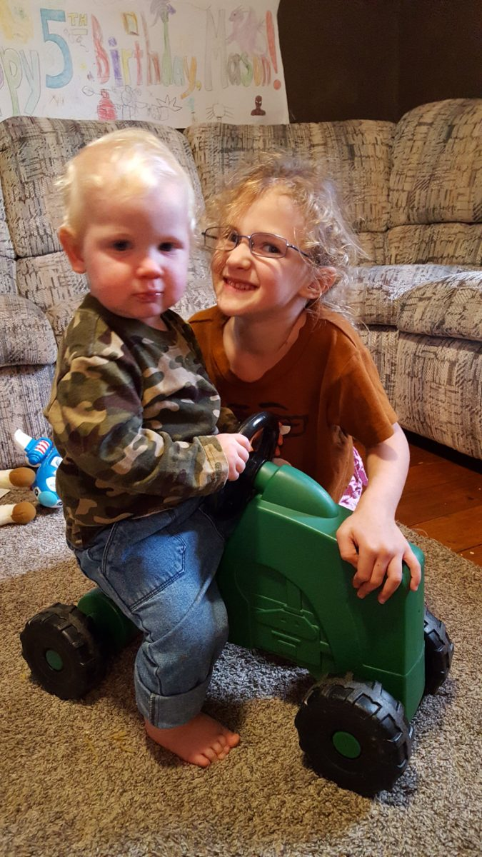 Day in the life of a mom of seven children toddler boy riding a toy tractor with 6 year old sister wearing glasses