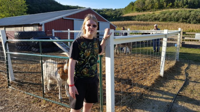 Day In The Life large family A teen girl wearing glasses with goats shed fence behind her