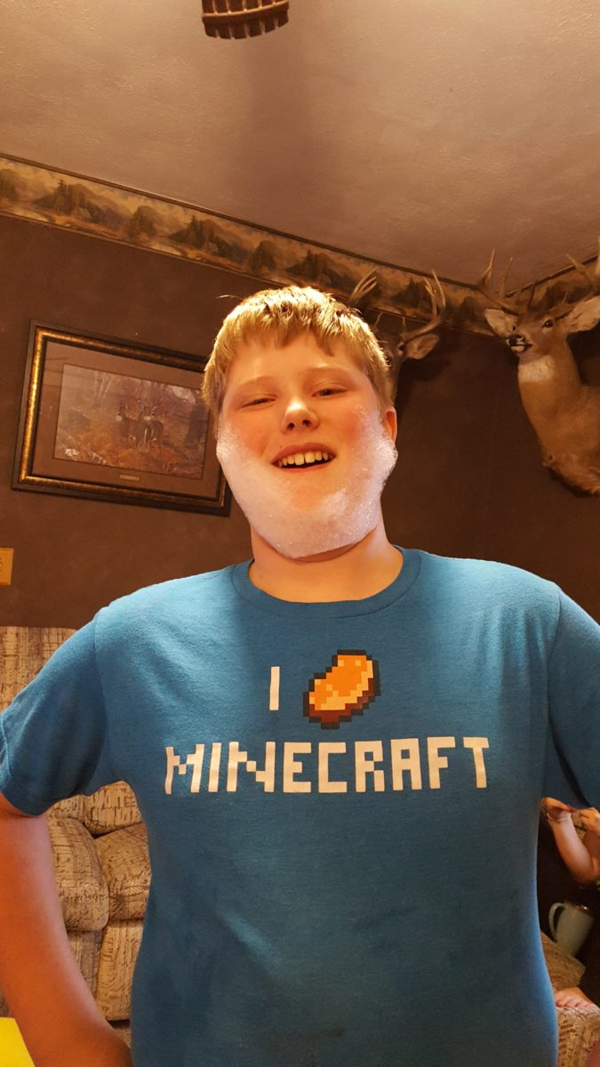 Day In The Life Large Family Style a 12 year old boy wearing a minecraft shirt and a bubble beard in a den deer mounts background