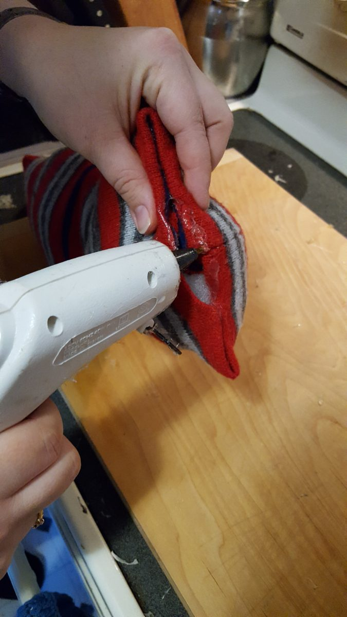 How To Hot Glue A Christmas Snowman Pillow So You Don't Have To Sew It glue gun hand holding material