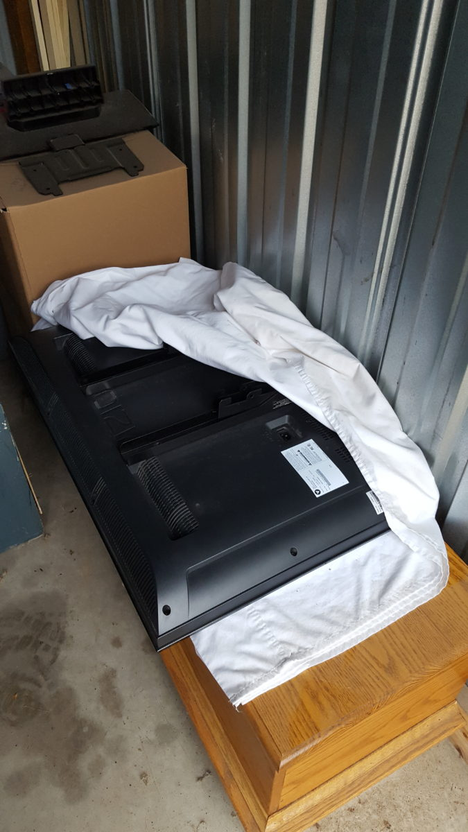 a tv about to be covered by a sheet in a storage unit How To Keep Your Storage Unit Items Safe