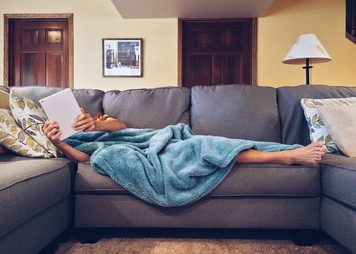 person using electronic device laying on couch with pillows blanket lamp pictures