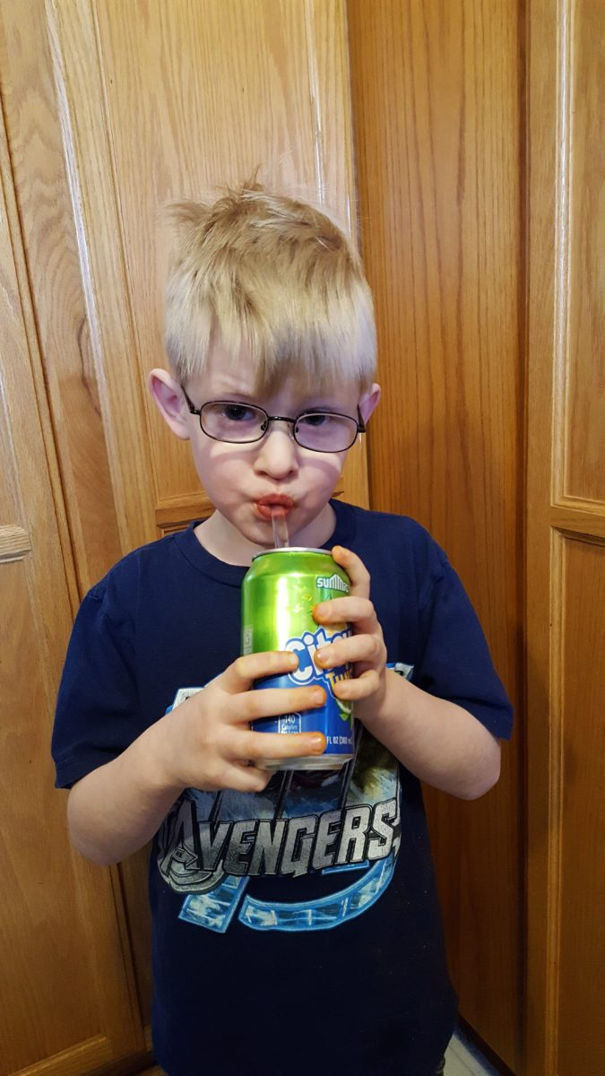 blonde preschool aged boy with glasses drinking a soda pop with a glass straw wearing an Avengers shirt standing in a kitchen