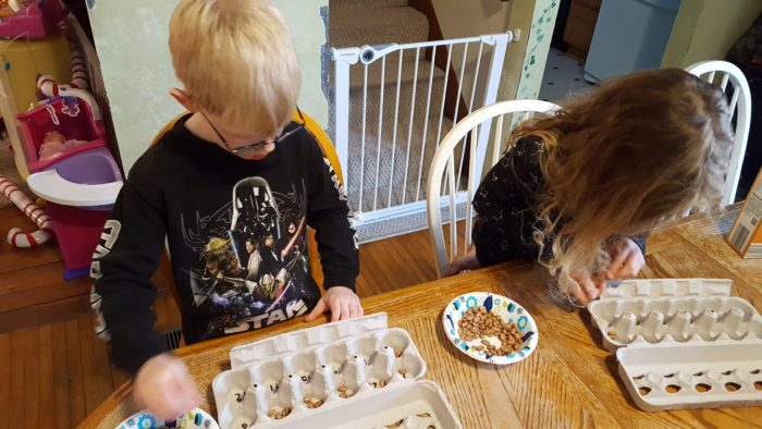 Preschool children counting beans and placing them in egg cartons