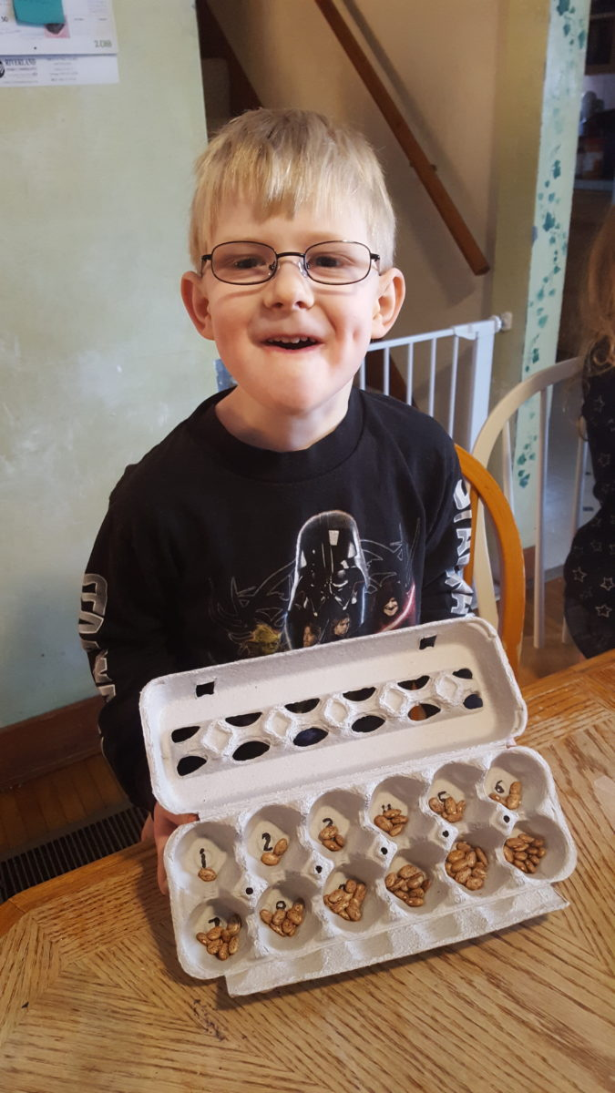 young boy showing how he counted beans into egg carton slots
