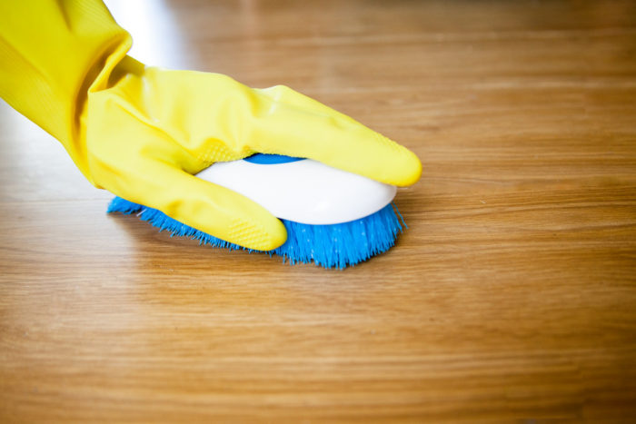 hand with yellow rubber glove and scrub brush scrubbing wood floor 4 Essential Things You Need For A Big Clean / Spring Cleaning / Deep Cleaning