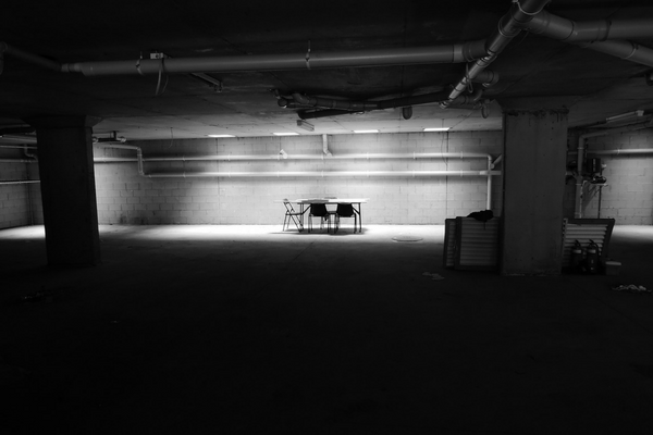 black and white photo of card table set up in a barren basement Getting To The Bottom Of Bumps In Your Basement