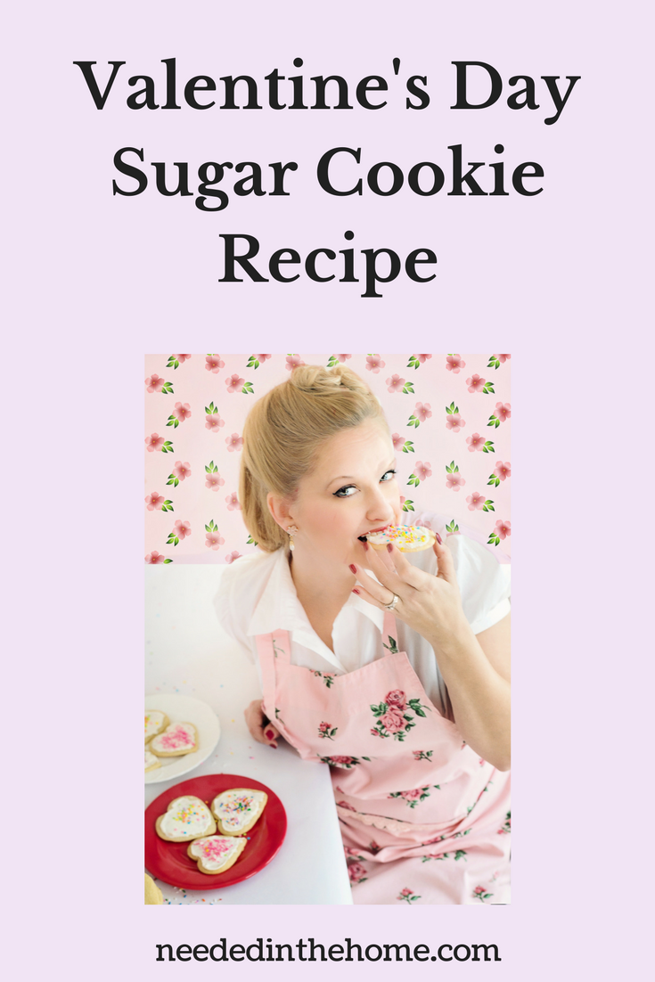 Valentine's Day Sugar Cookie Recipe blond woman in an apron biting into a heart shaped frosted sprinkled cookie neededinthehome.com