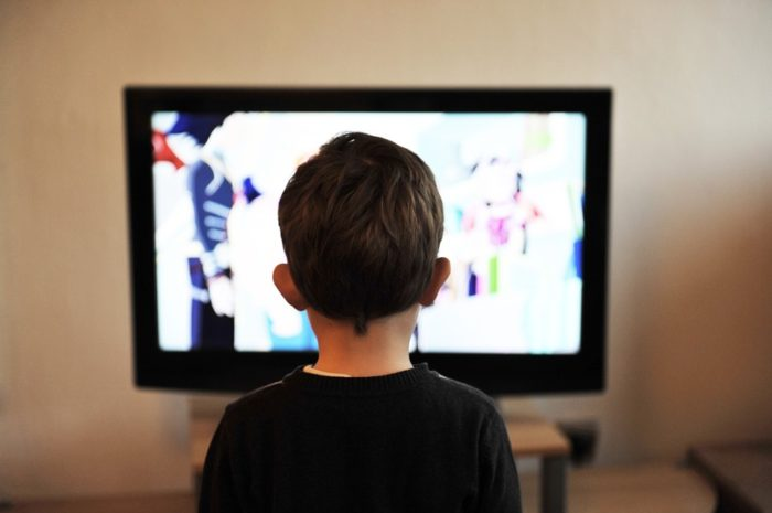 young boy sitting in front of television Save Yourself Stress By Keeping Your Kid At Their Best During School Days