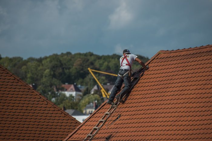 man on roof putting in a new roof up high renovating an older home