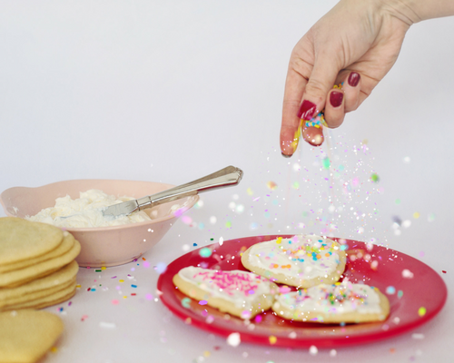 hand sprinkling sugar on heart shaped sugar cookies frosting knife Valentine's Day Sugar Cookie Recipe