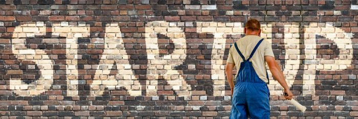 man painting startup on a brick wall Questions You Should Ask Before Starting a Business