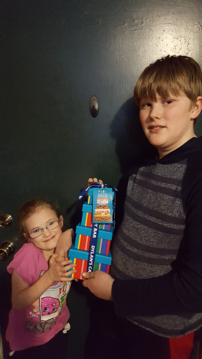 young girl in glasses and pink shirt preteen boy in striped shirt holding Dylan's Candy Bar Chocolate Sweet Treat Tower for product review