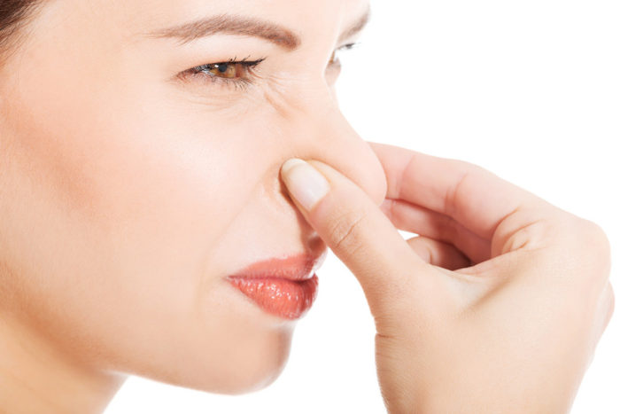 woman holding her nose for a foul smell in the kitchen