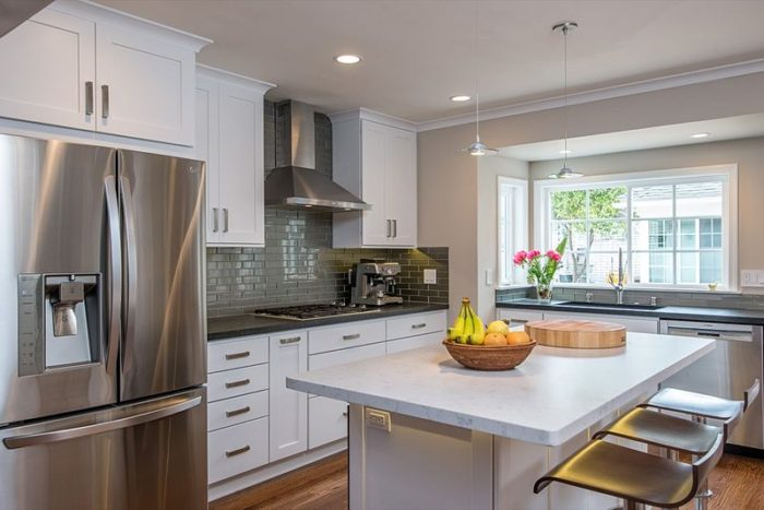 white cupboards marble counter kitchen stainless steel seats fridge hood stovetop sink fruit basket window lighting