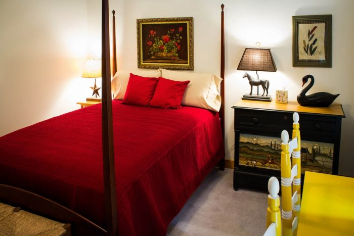 bed with red bedspread dresser table chairs guest room Turning Guesties Into Besties With Your Guest Room