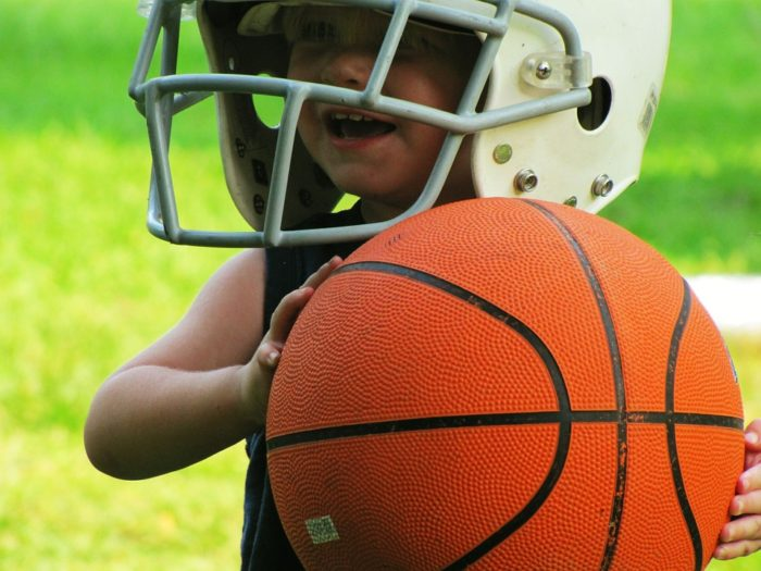 young boy in football helmet holding a basketball green grass outside growing the kids up healthy when parenting