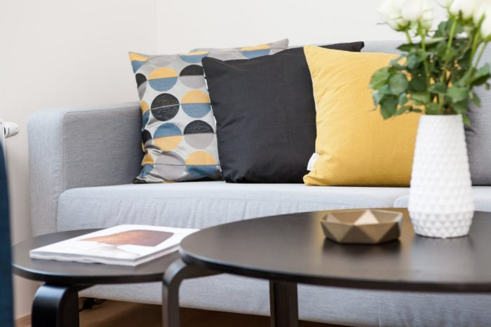 couch cushions pillows vase flowers magazine coffee tables living room scene getting your home ready for summer