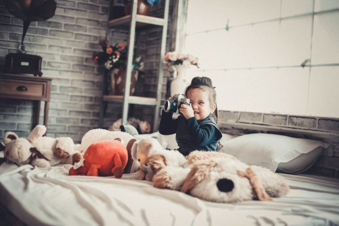 little girl in bed camera stuffed animals shelves pillow what could really liven up your family home