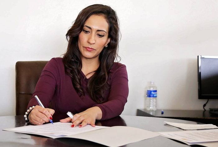 woman signing a document with a pen at a desk What Are The Biggest Obstacles Facing A Home-Based Mompreneur?