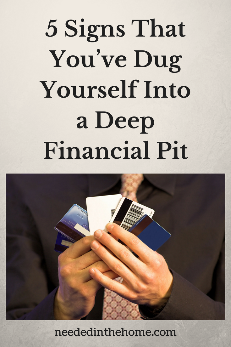5 Signs That You've Dug Yourself Into a Deep Financial Pit man holding credit cards fanned out neededinthehome