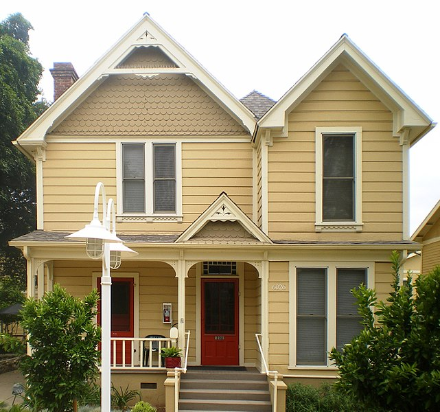 yellow two story home with porch red doors shrubs steps ensure your home is in tip top shape before going on holiday