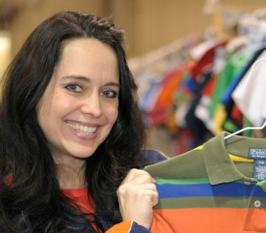dark haired woman holding a boys shirt on a hanger at a JBF consignment sale how to resell children's items