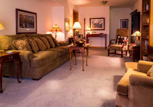 finished basement family room couch chair lamps Basement Conversions: The Pros & Cons of Remodeling