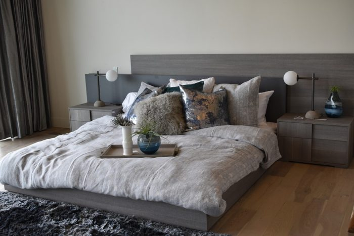 Everything You Need to Know About Carrying Out a Bedroom Makeover / Master Bedroom Makeover Ideas queen size bed tray of plants lamps headboard curtains hardwood floors area rug nightstand