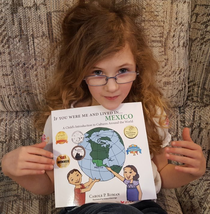 Product Review of If You Were Me And Lived In Mexico paperback book by Carole P. Roman blond girl wearing glasses holding book