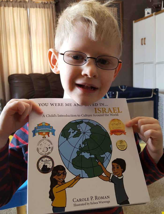 Product Review of If You Were Me And Lived In Israel paperback book by Carole P. Roman blond boy wearing glasses holding book