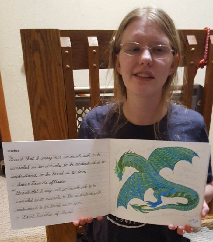a young adult woman in glasses and blond hair holds the art of cursive writing workbook open to show her colored dragon and handwriting