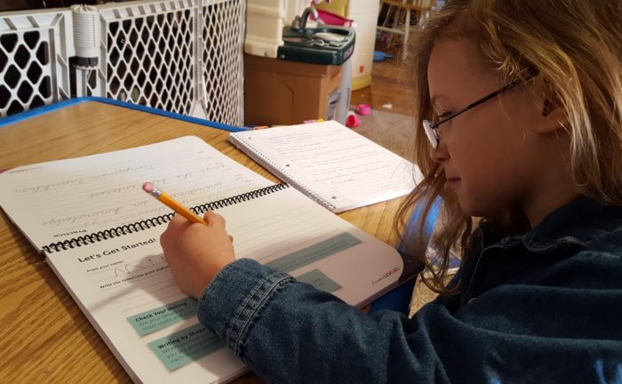 a girl in glasses writes left handed in the cursive writing workbook with the cursivelogic program