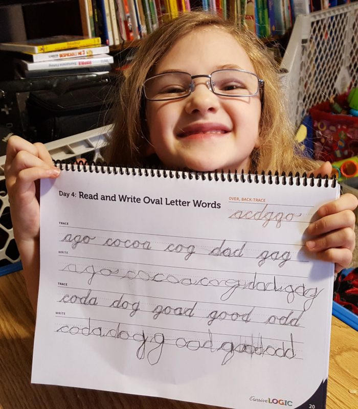 a seven year old girl in glasses holds up her cursive writing book to proudly show what she learned in the cursivelogic writing program
