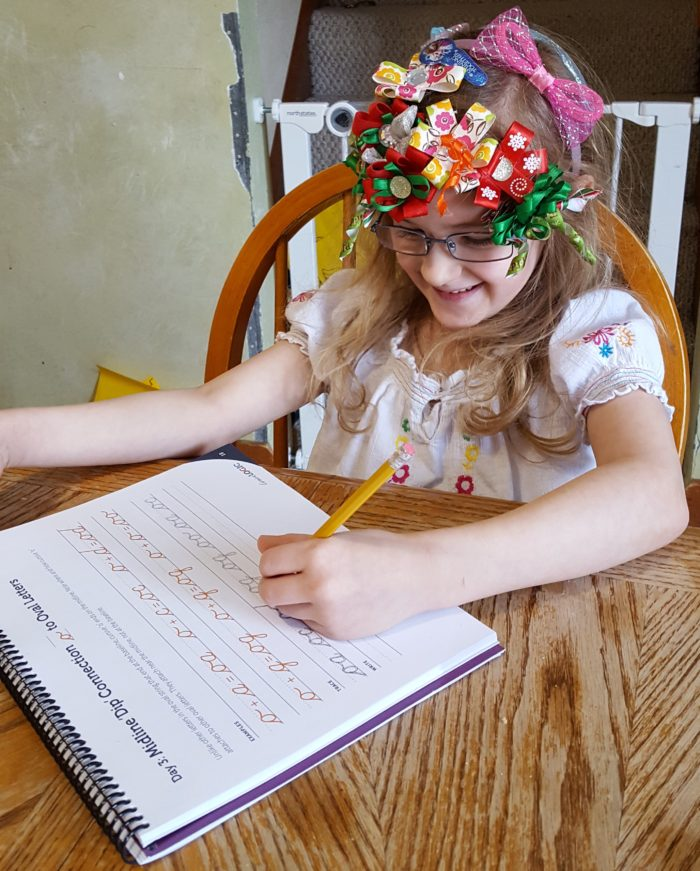 a young girl in glasses and bows in her hair writes left handed with the cursivelogic writing book