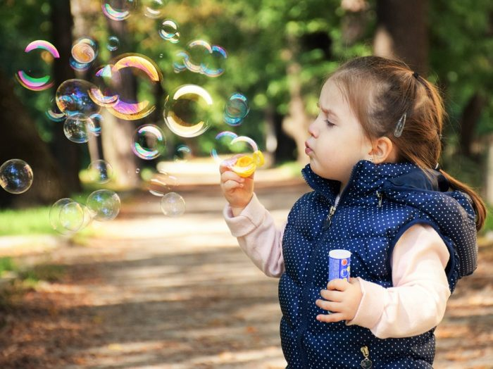 Simple Ways To Keep Your Kids Out Of Trouble young girl blowing bubbles outside