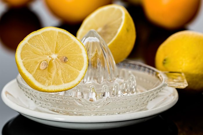 cut lemons on glass lemon juicer and plate Using Lemon Juice When Cleaning Household Realities You Can't Life Hack