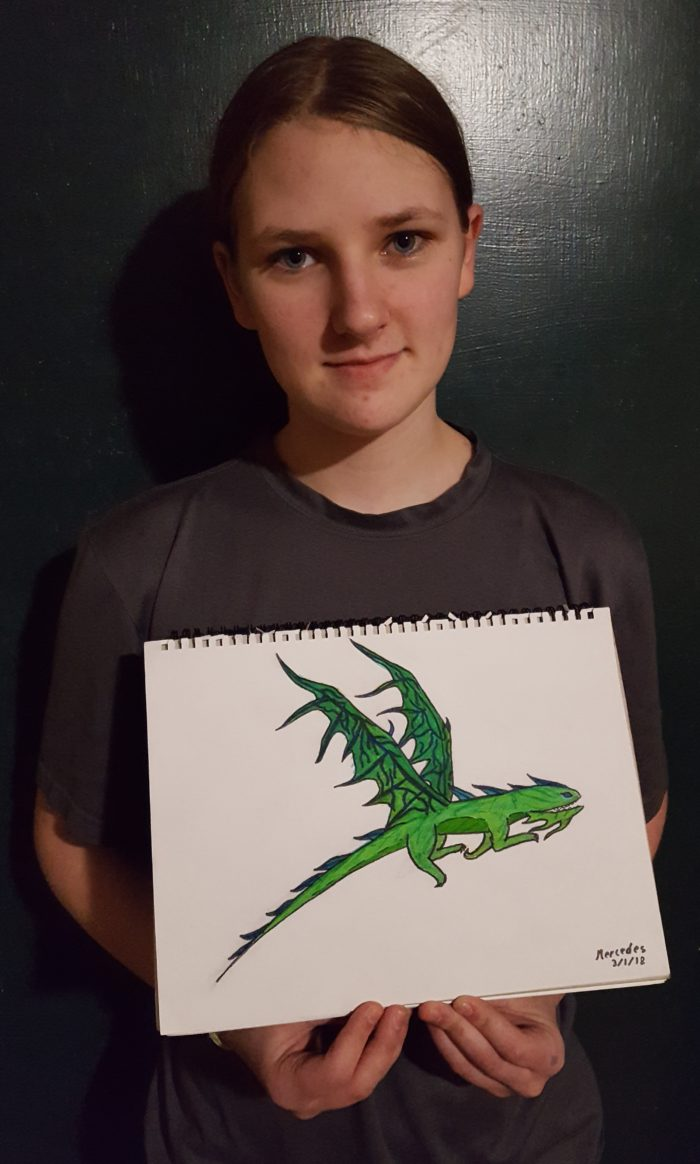 a teen girl holds her marker ink cartoon drawing of a flight mare dragon inspired from How To Train Your Dragon made by using Magic Stix Washable Markers in product review Mercedes 2018