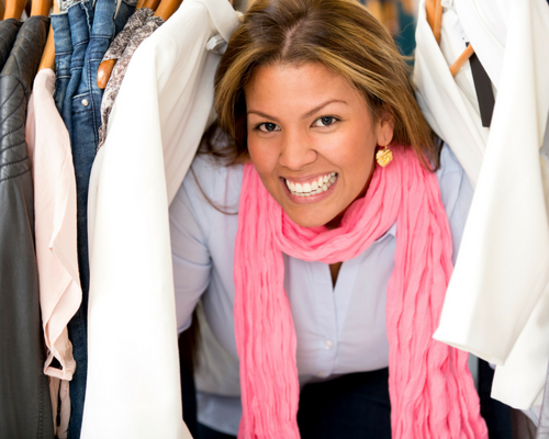 Live with the minimal amount of clothing with your capsule wardrobe with your new minimalist lifestyle woman peeking through her clothing in the closet pink scarf