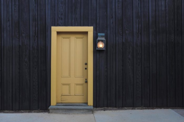 Does your dream home have privacy? black wooden walls on exterior of home with yellow door and lamplight