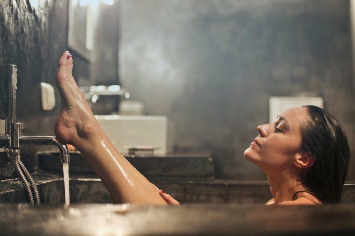 Designer Bathroom woman in bath with water running