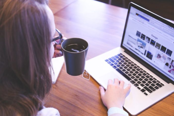 organization hacks for the home office woman holding tea looking at laptop